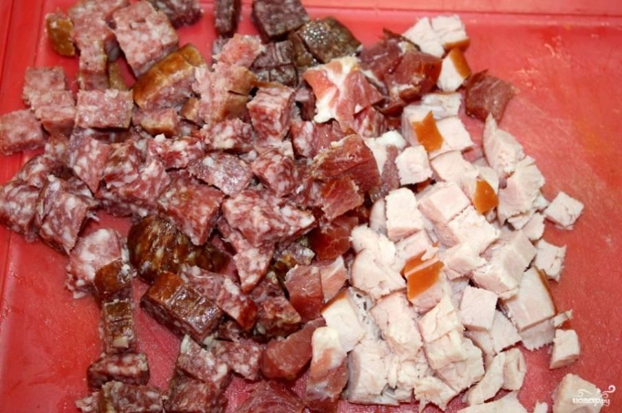 Нарежьте кубиками ветчинку, колбасу, бекон и другие мясные продукты.