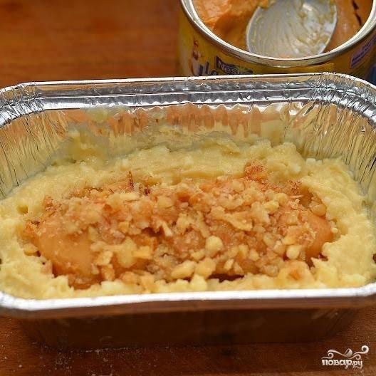Берем форму для выпекания, смазываем ее маслом. На дно кладем немного нашего теста, затем посередине кладем пару чайных ложек сгущенки, и сверху вновь кладем тесто.