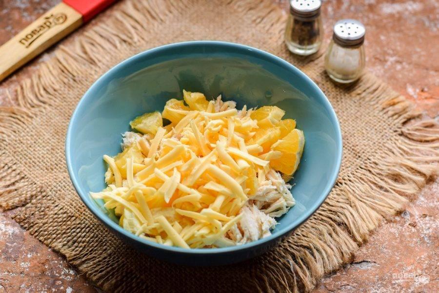 Твердый сыр натрите на средней терке и добавьте в миску к курице и апельсину.