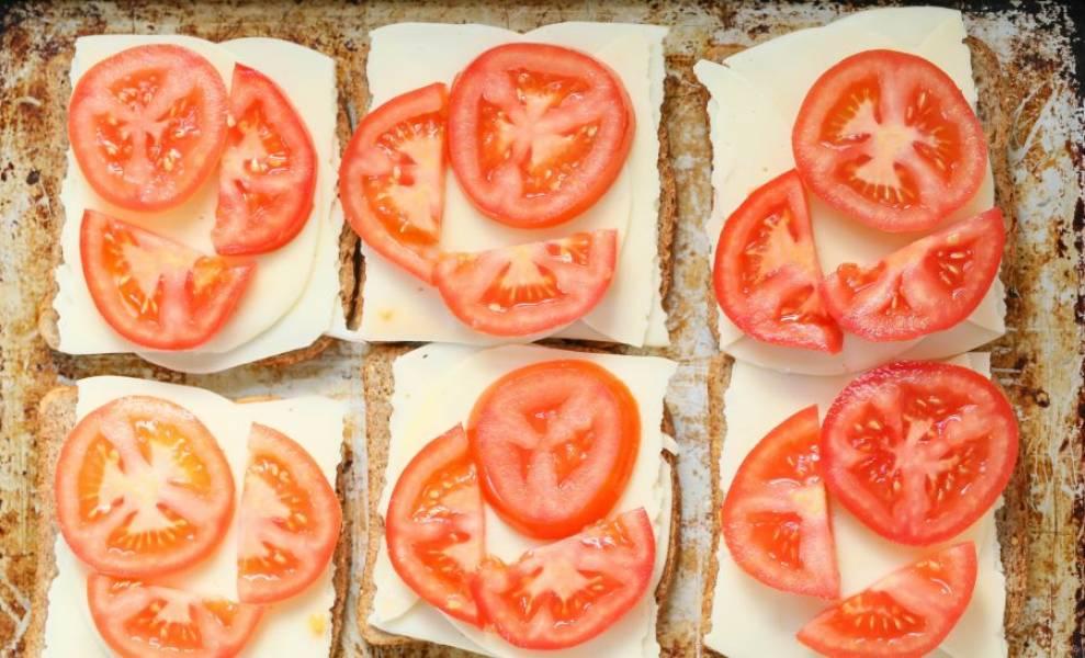 Вымойте и нарежьте тонко томаты, уложите их поверх сыра (примерно по 2-3 кусочка на ломтик).