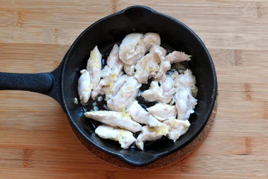 Сразу же следом положите в сковороду куриное филе, нарезанное небольшими косыми полосками. Добавьте сахар и перемешайте. Быстро обжарьте до позолоты.