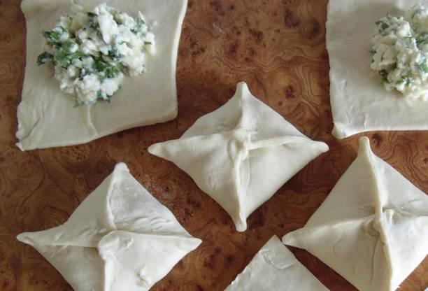 Тоненько раскатайте тесто, разделите его на квадратные кусочки. Выложите в центр каждого кусочка начинку. Заверните края теста кверху, защипните, сформировав слоечки.