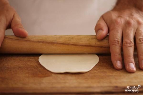 Уже готовое тесто разрезаем на небольшие кусочки, каждый из которых раскатываем в тонкий пласт - так. как на фото.