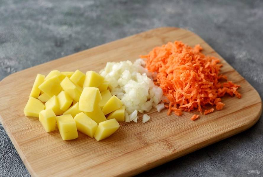 Картофель помойте, очистите, нарежьте кубиками. Морковь помойте, очистите, натрите на крупной терке. Лук нарежьте мелкими кубами. Чечевицу промойте.