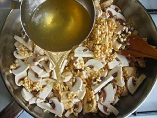 Затем добавьте грибы, еще четверть бульона и немного соли.