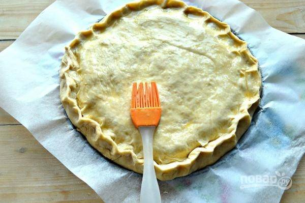 11. Накройте пирог вторым пластом теста. Защипните края. Взбейте желток, смажьте им пирог. Отправьте в разогретую до 180 градусов духовку.
