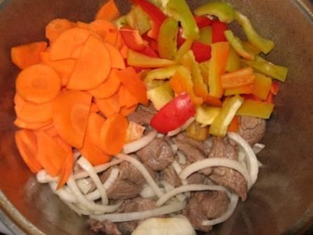 Пока мясо жарится, чистим морковь и режем ее кружочками, лук нарезаем полукольцами, перец брусками, помидоры дольками. Как только мясо обжарится, выкладываем в казан лук, жарим все 3-4 минуты, затем добавляем помидоры и перец, продолжаем жарить все в течение 5-6 минут.