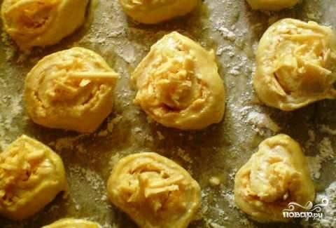 Порубите чеснок и выложите его к начинке. Затем сверните тесто с сыром рулетиком. Разрежьте его на равные части, чтобы получились булочки.