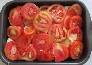 Отправит кабачки в разогретую до 200 градусов духовку на 10-15 минут. Тем временем помыть и порезать кружочками помидоры. Вынуть кабачки, положить на них помидоры и снова запекать в духовке 10 минут.