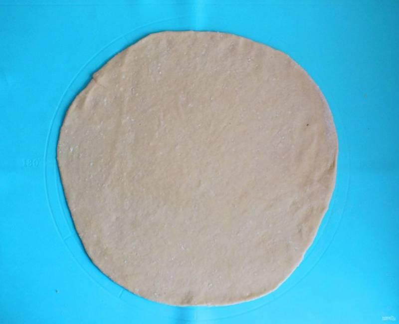 Раскатайте меньшую часть теста в пласт. Ориентировочный диаметр 32 см.