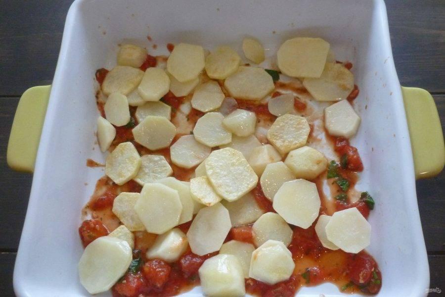 В квадратную форму для запекания налейте немного соуса. Выложите картофель. Приправьте солью и перцем.