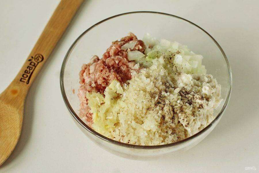 В глубокой миске соедините фарш, измельченный чеснок, нарезанную мелкими кубиками луковицу, отжатый от молока батон и 3 ст. ложки риса. Посолите, поперчите по желанию и все хорошо перемешайте.