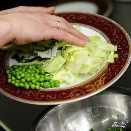 Смешиваем все подготовленные ингредиенты - салат, зелень, мяту, горошек и огурцы.