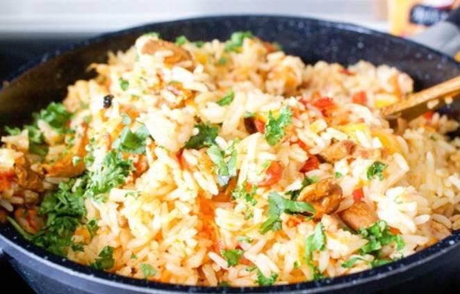 В конце, когда рис впитает в себя всю жидкость, добавьте измельченную зелень и перемешайте блюдо. Приятного аппетита!