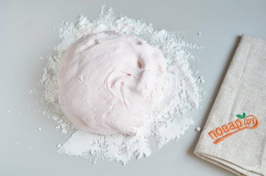 9. Притрусите стол сахарной пудрой, переложите мастику и руками продолжайте вымешивать ее.