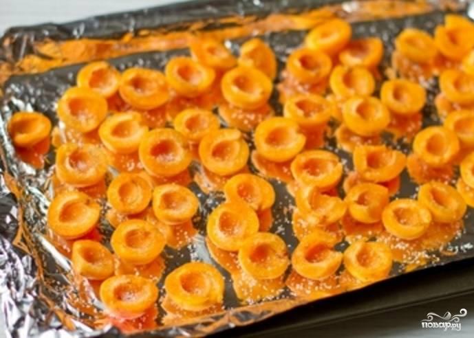 Удалите из абрикосов косточки. Разогрейте духовку до 200 градусов. Оставьте пару фруктов для украшения. Остальные посыпьте 1 ст. ложкой сахара и уложите на противень, который нужно застелить фольгой. Отправляем абрикосы печься на 10 минут. В это время разводим желатин: заливаем его 3 ст. ложками воды и оставляем для набухания.
