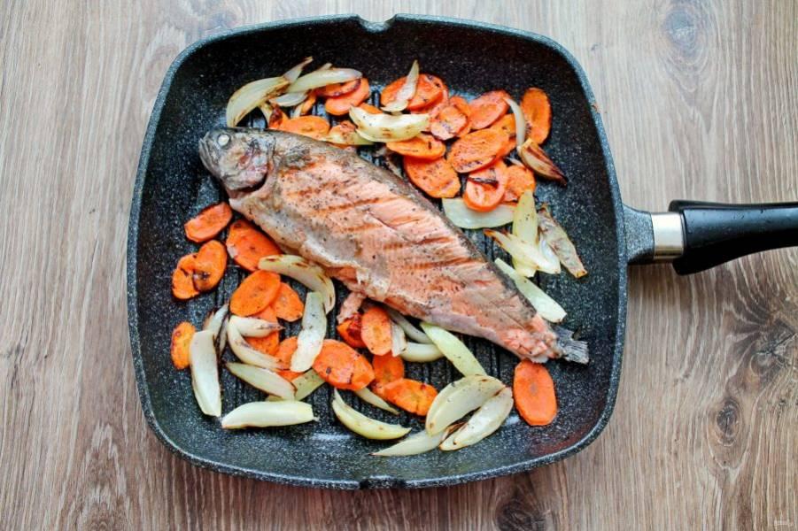Раздвиньте овощи, и выложите форель.