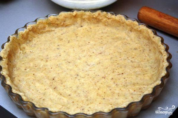 Спустя полчаса делим тесто на две части - 1/3 и 2/3. Ту часть, что побольше, раскатываем и выкладываем в форму для выпекания - как показано на фото. Ставим форму для выпекания в духовку и выпекаем 15 минут при 180 градусах.