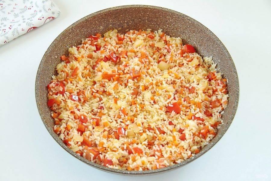 Добавьте промытый рис и продолжайте обжаривать все вместе, пока рис не станет прозрачным.