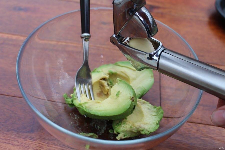 Мягкое авокадо переложите в тарелку. Выдавите к нему чеснок через пресс. Добавьте майонез.