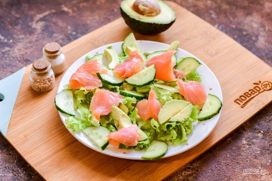 Поверх салата разложите небольшие кусочки форели. Сбрызните салат слегка маслом, по желанию лимонным соком, добавьте соль и перец.