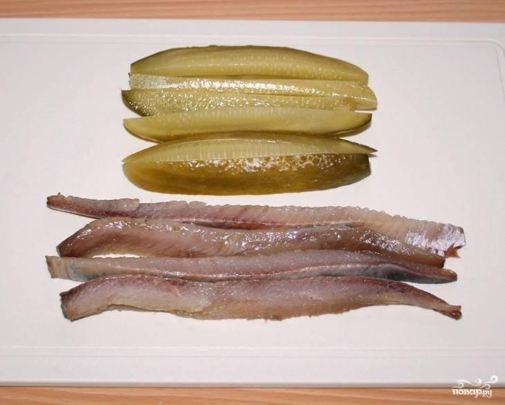 Заранее подготовьте все ингредиенты. Поставьте вариться или запекаться свеклу, отварите яйца. Нарежьте рыбное филе длинными тонкими кусочками. Аналогичным образом нарежьте и солёные огурцы. Их можно очистить от шкурки, но это совсем необязательно.