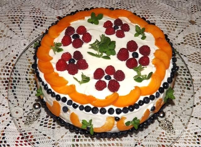 Выложите поверх крема на первый корж тонко порезанные кусочки абрикосов, можно добавить в прослойку и чернику, она не сильно крупная, выпирать не будет. Затем уложите верхний корж и обмажьте кремом торт со всех сторон. Украсьте ягодами и фруктами.