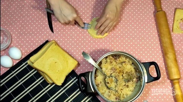 6.Выложите на одну часть хлеба начинку, накройте второй частью, прижмите края вилкой.
