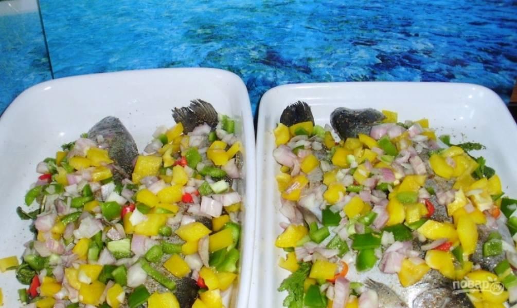 В противень, смазанный растительным маслом, выложите рыбку. Сверху на нее выложите подготовленные овощи и полейте маринадом. Накройте рыбу фольгой, чтоб она не подгорела в процессе готовки.