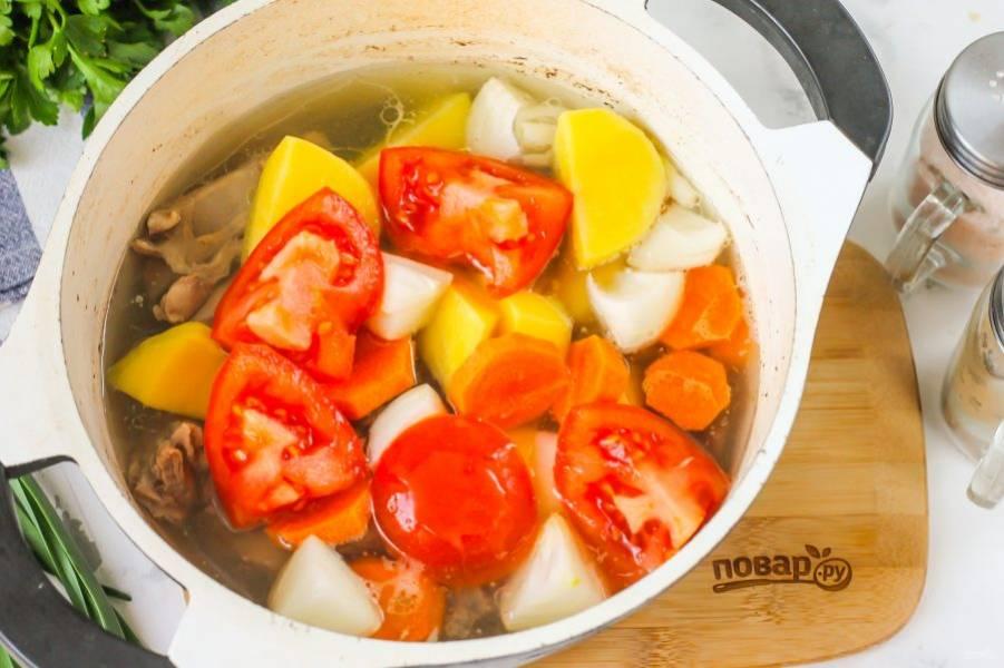 Промойте помидор и вырежьте зеленую сердцевинку. Нарежьте крупными кусочками и добавьте в емкость. Варите суп еще 30-40 минут.