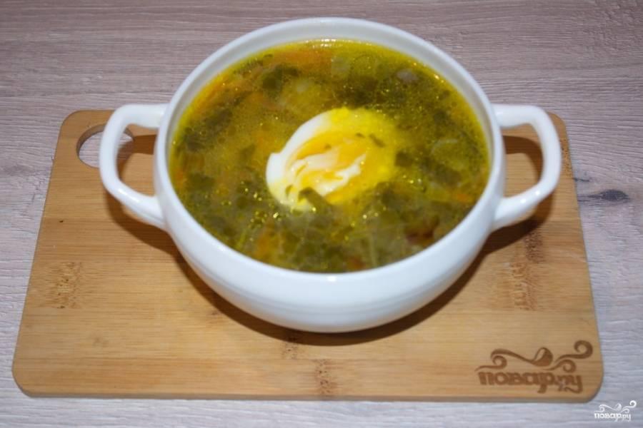 Отдельно отварите яйца вкрутую. Порционно разлейте готовый суп по тарелочкам. Добавьте по половинке яичка в каждую порцию, подайте супчик к столу.