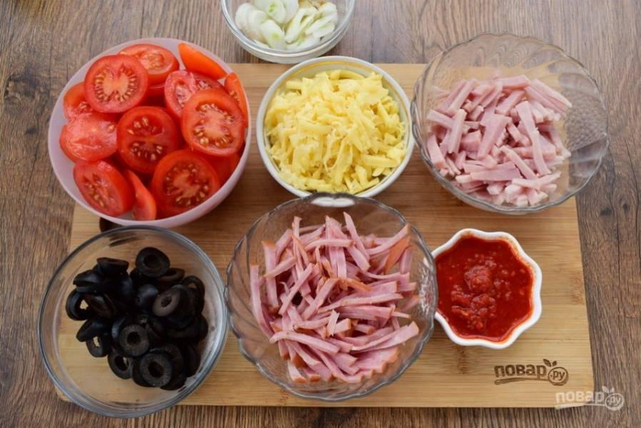 Колбасу и ветчину нарежьте тонкой соломкой. Маслины — тонкими колечками, помидоры —  ломтиками.