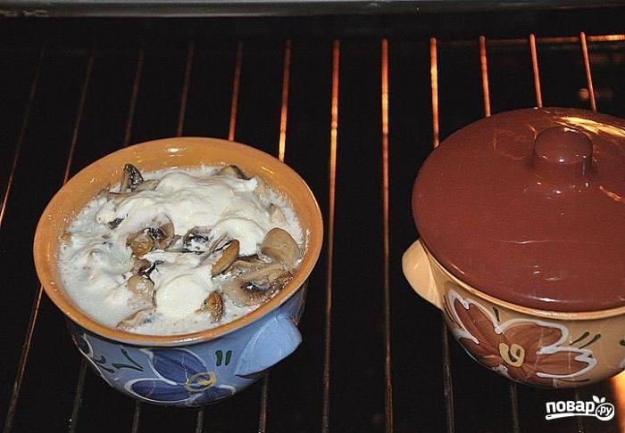 3.Для соуса: в миске смешиваю сметану с тертым сыром и натертым хреном. Грибы чищу и мою, нарезаю небольшими пластинами. В каждый горшочек укладываю пельмени, затем вливаю бульон (но не заливаю), кладу грибы и сверху кладу соус.