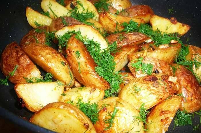 Разогреваем в сковороде растительное масло и обжариваем на сильном огне картофель до золотистого цвета. Затем накрываем его крышкой и жарим на медленном огне 5-7 минут. При подаче на стол присыпаем измельченным укропом и чесноком. Приятного аппетита!