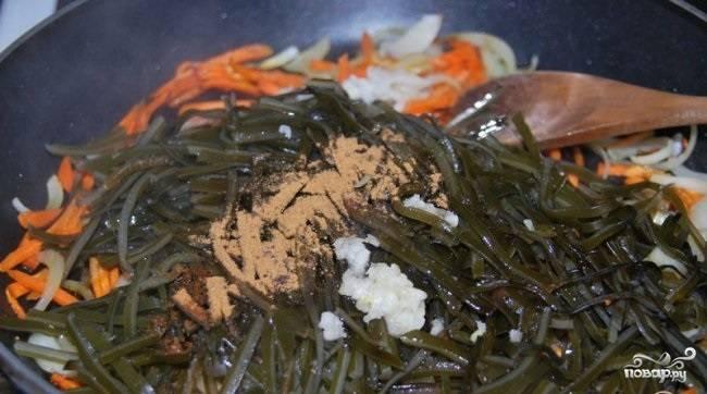 3.В сковороду к овощам добавляем отваренную морскую капусту, чистим и выдавливаем чеснок, вливаем соевый соус, уксус и кунжутное масло, насыпаем по вкусу красный и черный перцы. Перемешиваем, накрываем крышкой и выключаем, настаиваем до остывания или минимум 30-40 минут.