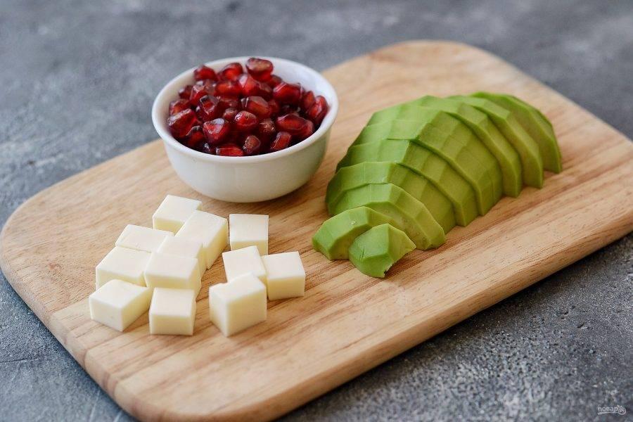 Авокадо очистите от кожуры, удалите косточку и нарежьте дольками. Сыр нарежьте кубиками, зерна граната отделите от перегородок и кожуры.