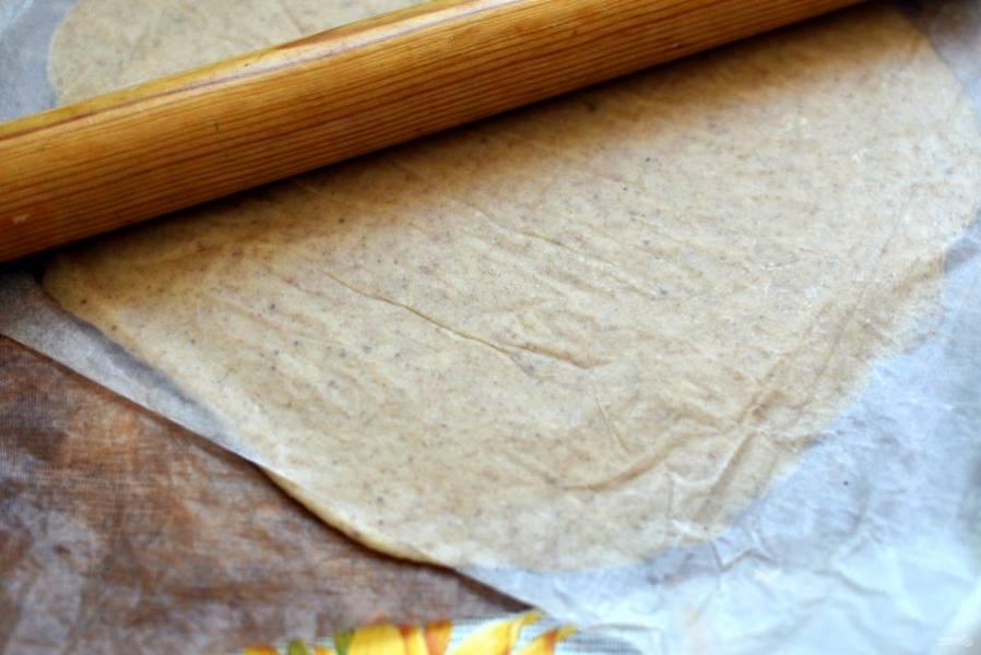 Раскатайте тесто на коврике для выпечки или пергаменте, накрыв сверху бумагой для выпечки. Раскатывайте края чуть тоньше середины. Подходящей тарелкой наметьте слегка контур круга в центре, так ваша галета выйдет более ровной.