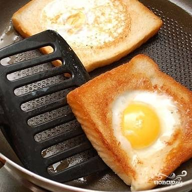 5. Через две минуты переверните хлеб с яйцом на другую сторону и жарьте еще минутку-две.