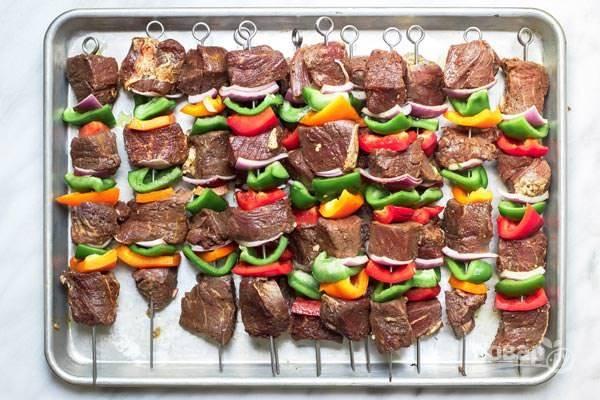 4.Достаньте мясо из холодильника и оставьте на 15 минут. Очистите перцы и нарежьте их небольшими кубиками, очистите и нарежьте крупно луковицу. Распределите мясо и овощи между шампурами.