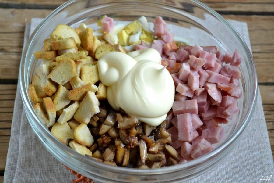 Смешайте ветчину и яйца с обжаренными грибами и сухариками. Заправьте все майонезом.