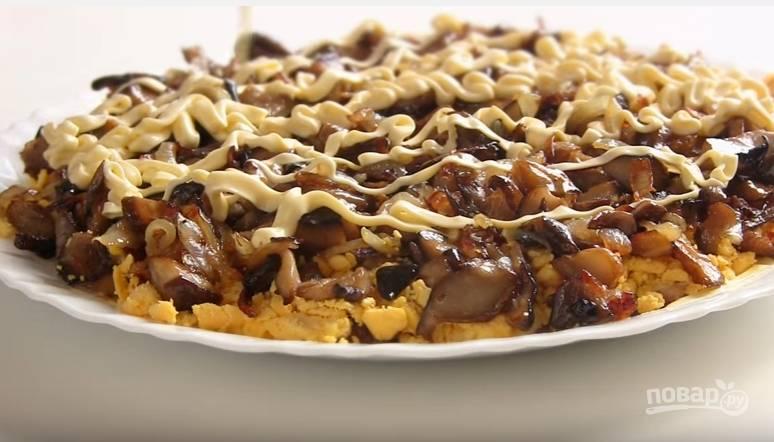 4. Третьим слоем выложите жареные грибы и сделайте сеточку из майонеза.