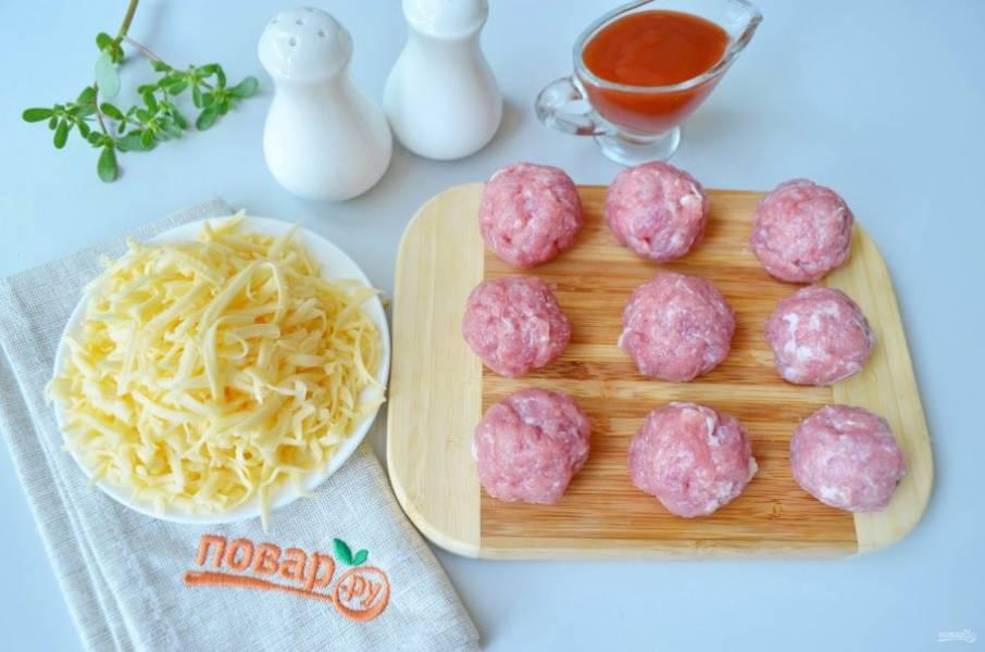 Свинину порежьте кусочками, перекрутите на мясорубке или используйте блендер. Посолите и поперчите фарш, скатайте 12 шариков. Твердый сыр натрите на крупной терке.