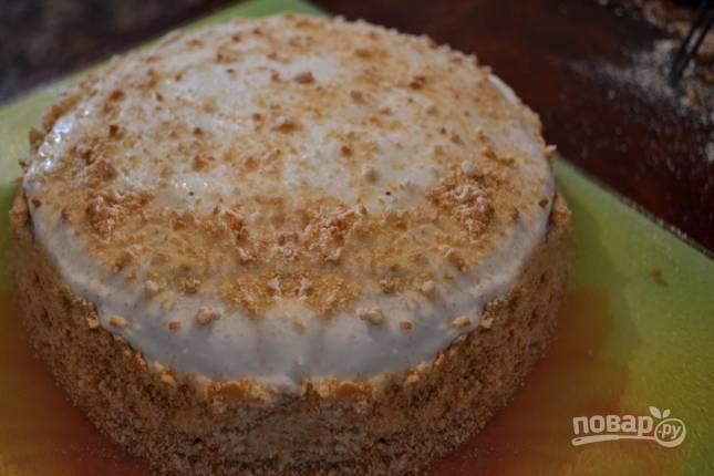 Смазываем кремом бока торта и последний корж. Бока торта густо посыпаем измельченными орехами.