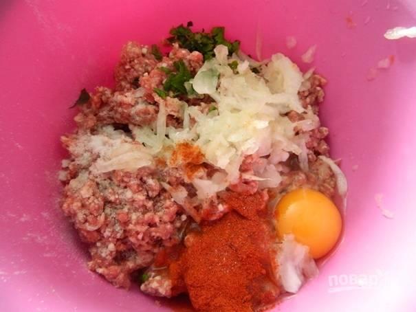 1. Добавляем к фаршу соль, специи, натертый на крупной терке лук, яйцо и немного зелени. Хорошо вымешиваем и отставляем в сторону.