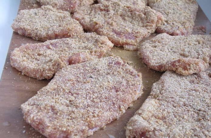 2. Затем нарезаем мясо кусочками толщиной не меньше 1 см. Отбиваем слегка молотком. Сухари смешаем с солью и перцем по вкусу. Яйцо взбиваем до однородности. Обмакиваем каждый кусок мясо в яйцо, затем посыпаем сухарями.