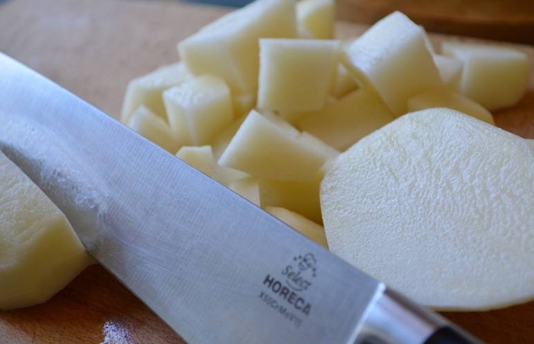 Картофель чистим и нарезаем его кубиками, выкладываем картофель в бульон и варим его 15-20 минут.