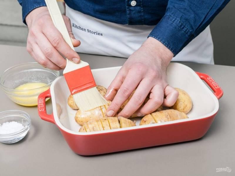 2. Затем расплавьте масло. Выложите на противень картофель. Далее смажьте его маслом сверху, а также посыпьте солью.