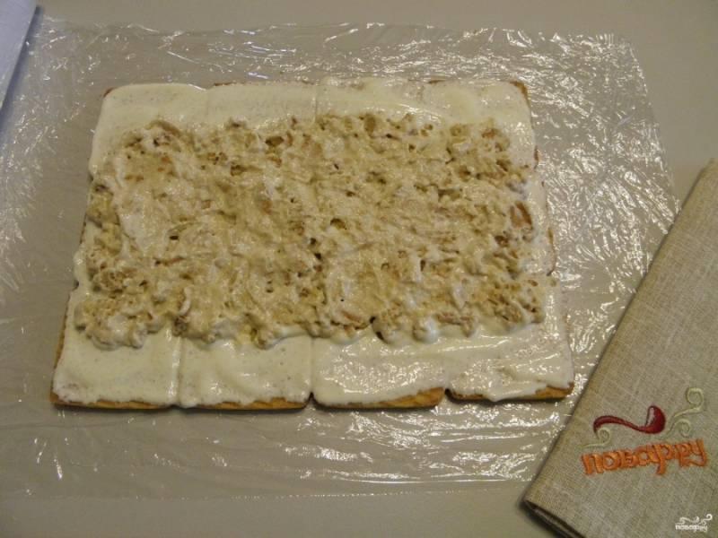 оставшуюся часть сметаны соедините с кусочками печенья, которое у Вас осталось. Перемешайте и выложите эту сладкую массу по середине, чуть отступив от края.