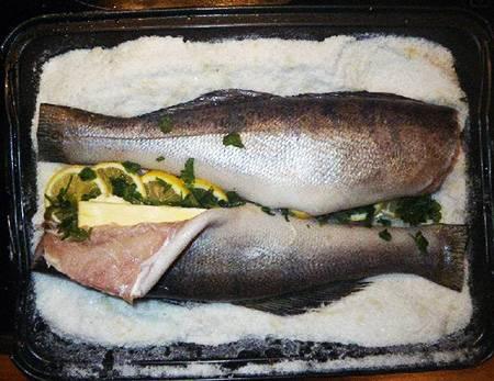 4. Что касается начинки, то тут все довольно просто. В данный рецепт приготовления запеченного судака в соли используется свежая зелень, любая, что есть под рукой, и ломтики лимона. Для сочность можно вложить кусочек сливочного масла или взбрызнуть рыбу оливковым.