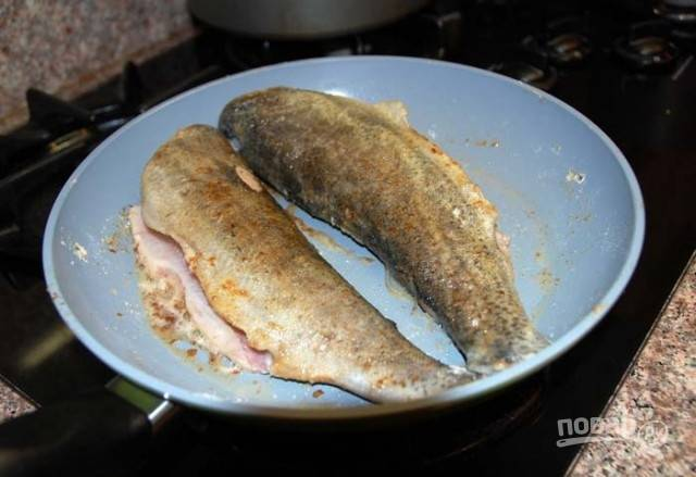 Выложите на сковороду заранее подготовленные тушки форели, обваленные в муке. Обжаривайте их с обеих сторон по несколько минут, периодически переворачивая рыбку.